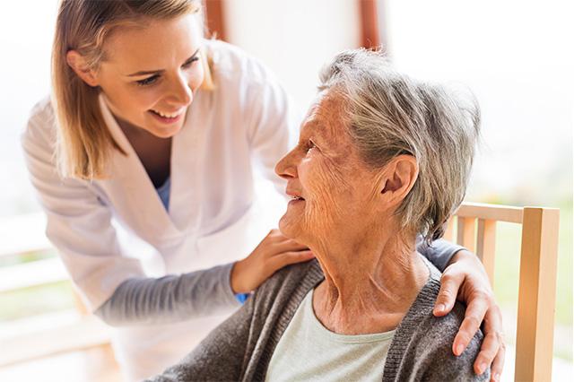 Pflegepersonal kümmert sich um Seniorin